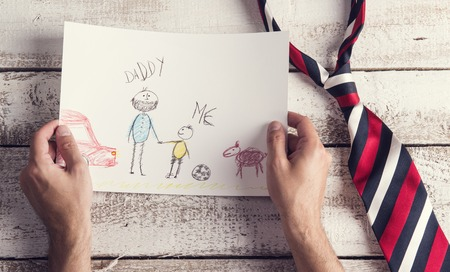 Fathers day composition with childs drawing and colorful tie laid on wooden desk backround. Stock Photo