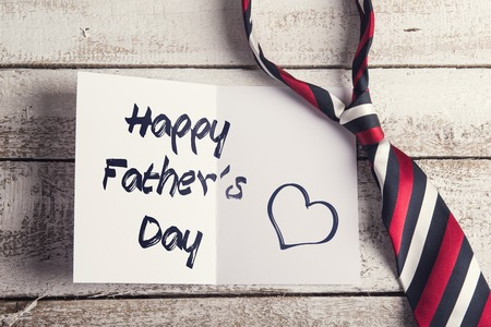 backround: Happy fathers day sign on paper and colorful tie laid on wooden floor backround.