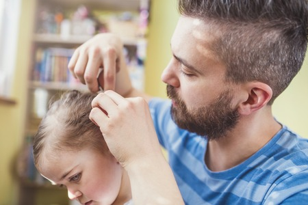 comb hair: Young father styling hair of his daughter Stock Photo