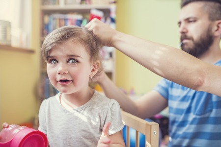dads: Young father styling hair of his daughter Stock Photo