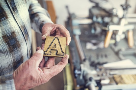 rarity: Senior man holding a letter that is used for engraving Stock Photo