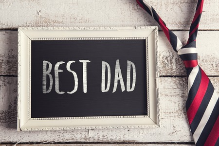 backround: Rectangle picture frame with Best dad sign and colorful tie laid on wooden floor backround.