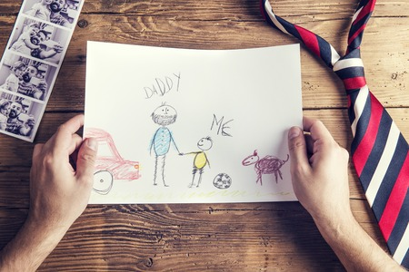 pictures of father and daughter, childs drawing and tie laid on wooden desk background.
