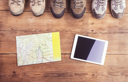 hiking shoes: Hiking shoes, map and tablet laid on a wooden floor background Stock Photo