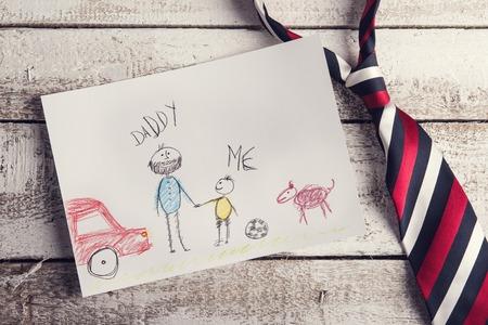 lazo regalo: Padres composición día con el dibujo del niño y colorido lazo establecido en el fondo de escritorio de madera. Foto de archivo
