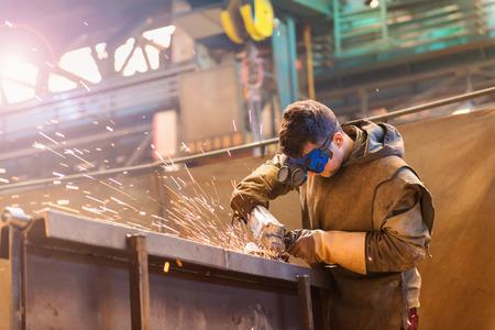 soldadura: Hombre joven con gafas de protección de soldadura en una fábrica Foto de archivo