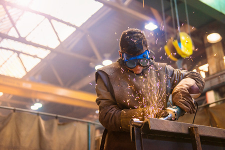 Young man with protective goggles welding in a factory