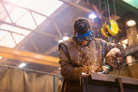 ouvrier: Jeune homme avec des lunettes de protection de soudure dans une usine