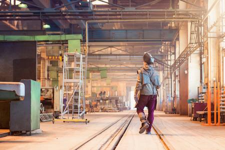 Jonge man in een fabriek in beschermende werkkleding Stockfoto