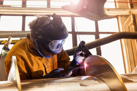 construction man: Young man with protective mask welding in a factory Stock Photo