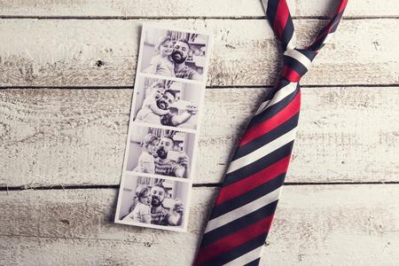 lazo regalo: fotos de padre e hija y colorido empate pusieron sobre fondo de madera piso. Foto de archivo