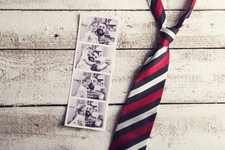 vintage photo:  pictures of father and daughter and colorful tie laid on wooden floor background.