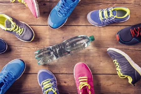 laid: Various running shoes laid on a wooden floor background