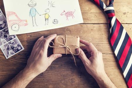 dog days: fotos del padre y la hija, dibujo del niño, presente y corbata establecido en el fondo de escritorio de madera.