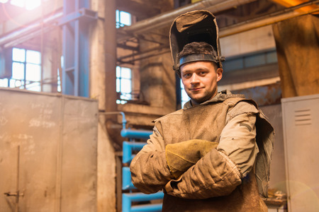Young man in a factory in protective workwear