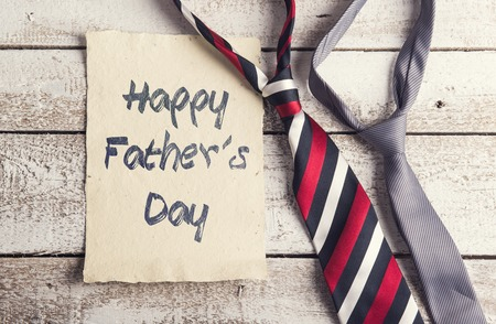Happy fathers day sign on paper and colorful ties laid on wooden floor backround.