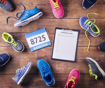 running race: Various running shoes, race number and running plan laid on a wooden floor background