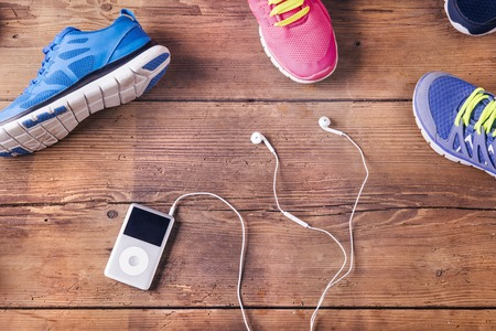 mp3 player: Various running shoes and mp3 player laid on a wooden floor background