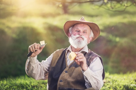 outside of the country: Senior farmer cutting and eating cheese outside in green nature Stock Photo