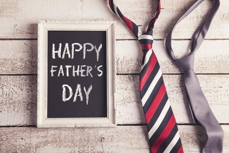 Rechthoek fotolijst met Happy vaders dag teken en twee gelegd op houten vloer backround banden.