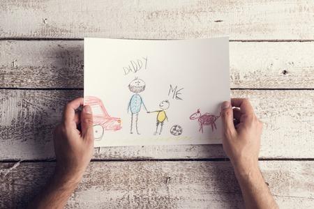 Vatertags Zusammensetzung mit Kinderzeichnung von einem Mann auf Schreibtisch aus Holz Hintergrund gelegt statt.