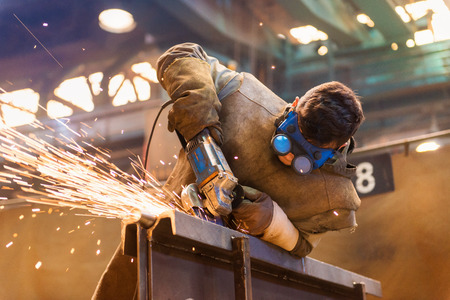 steel workers: Young man with protective goggles welding in a factory