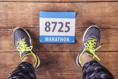 marathon runner: Unrecognizable young runner. Studio shot on wooden background.