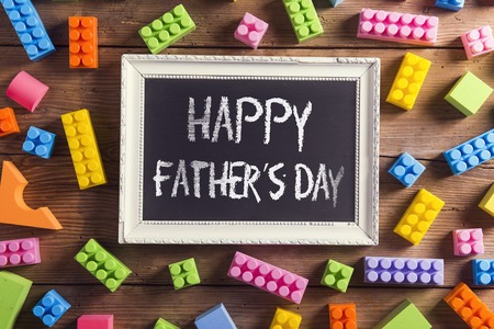 Picture frame with Happy fathers day sign laid on wooden . Stock Photo
