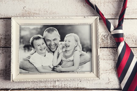 Picture frame with family photo and colorful tie laid on wooden background.