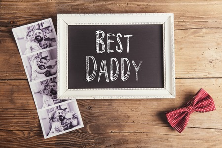 Picture frame with Best daddy sign, polaroid photos and bow tie on wooden background.