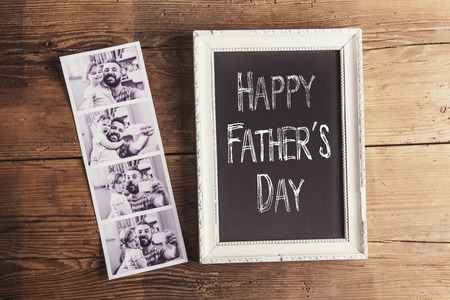 Picture frame with Happy fathers day sign and polaroid photos on wooden background. Stock Photo