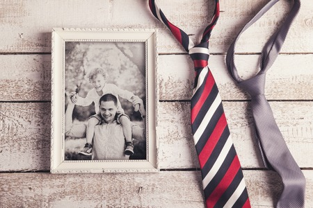 Picture frame with family photo and two ties laid on wooden .