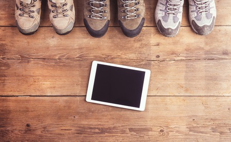 outdoor pursuit: Hiking shoes and tablet Stock Photo