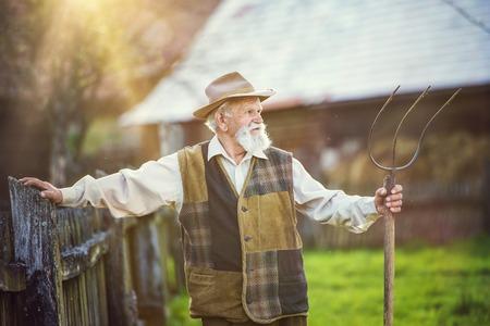 hayfork: Old farmer with pitchfork taking a break from work Stock Photo