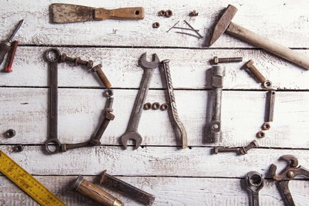 Desk of a carpenter with Dad sign and various tools. Studio shot on a wooden background. Imagens - 40286392