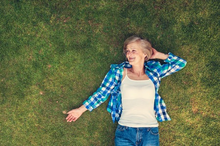 enjoying life: Beautiful senior woman lying on a grass in a park Stock Photo