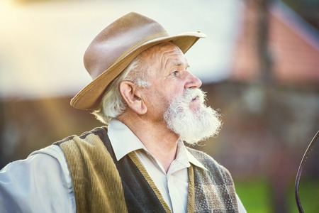 old farmer: Old farmer with pitchfork taking a break from work Stock Photo
