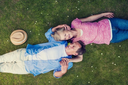 Beautiful seniors lying on a grass in a park hugging photo
