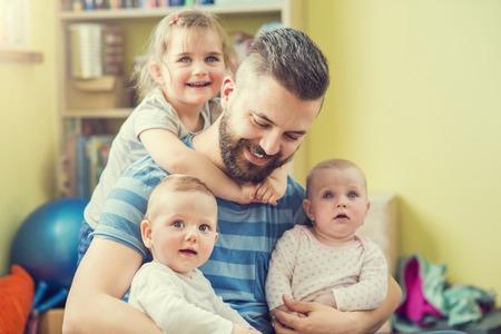 Jonge hipster vader knuffelen zijn schattige dochtertjes