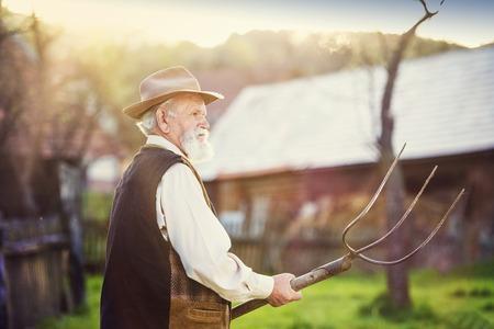 taking a break: Old farmer with pitchfork taking a break from work Stock Photo