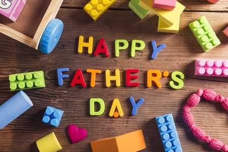 Happy fathers day sign and colorful toys laid on wooden . Stock Photo