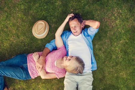 retirement couple: Beautiful seniors lying on a grass in a park hugging
