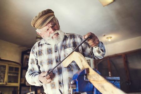 hombre viejo: Artesano mayor que trabaja con la alisadora en palo de madera en su taller