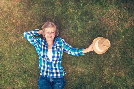 Beautiful senior woman lying on a grass in a park photo