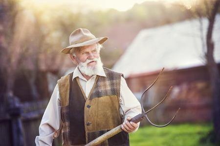 break from work: Old farmer with pitchfork taking a break from work Stock Photo