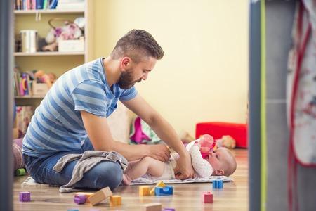 Un jeune père de hippie changer couche à sa petite fille de bébé