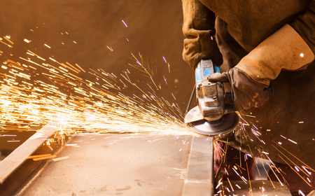 molinillo: Cierre de irreconocible joven de soldadura en una fábrica