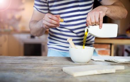 aceite de cocina: Hombre en la cocina preparando un aderezo para la ensalada de gambas Foto de archivo
