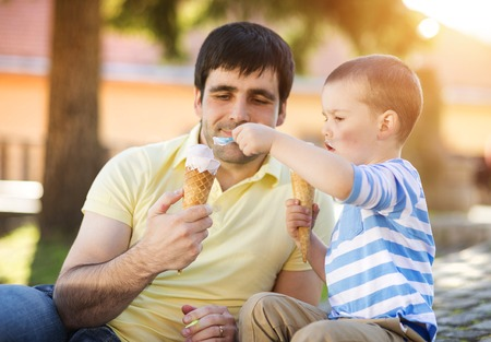 Father and son enjoying ice cream outside in a park Foto de archivo
