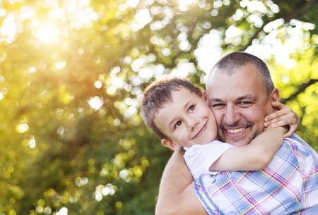 familias felices: Padre feliz con su hijo pasar tiempo juntos fuera en la naturaleza verde.